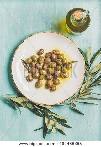 Pickled green Mediterranean olives on white ceramic plate, olive tree branch and virgin olive oil in glass bottle over light blue painted wooden background, top view