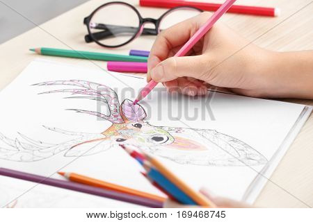 Woman coloring anti stress picture, closeup