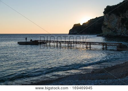 Wooden pier on the empty beach at sunset with lonely fisherman standing by the water