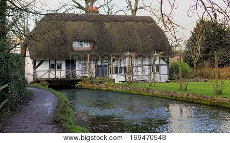 English mill cottage with Thatched roof built over a river