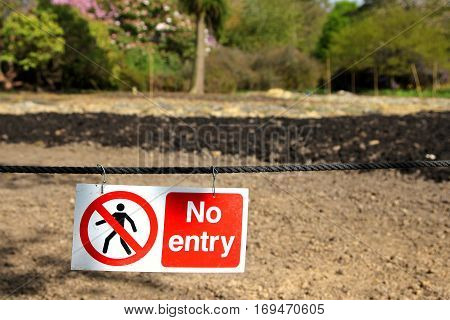 No entry sign hanging in front of some muddy ground