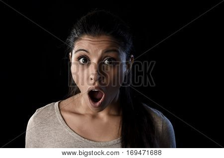 young beautiful scared Spanish woman in shock and surprise face expression astonished and amazed isolated on black background in primal facial emotion concept