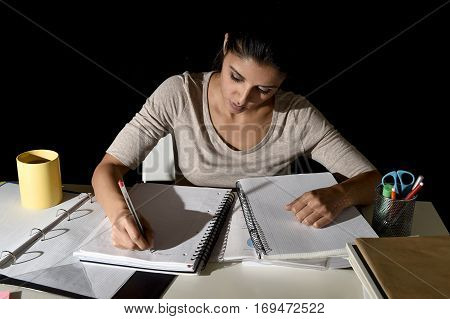 young busy beautiful Spanish girl studying at home late night looking preparing exam concentrated and quiet in education stress concept