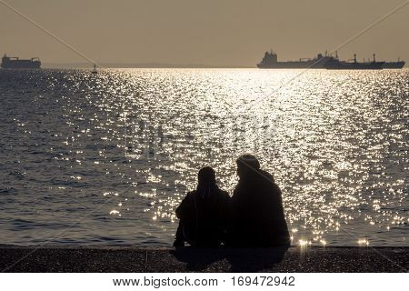 Two lovers looking at the Aegean Sea at sunset in Thessaloniki Greece