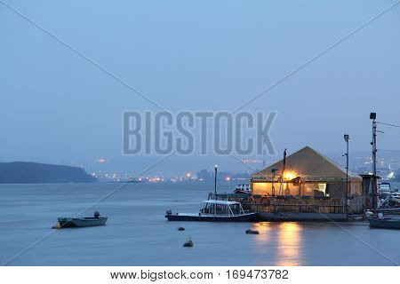 BELGRADE SERBIA - MARCH 7 2015: Restaurant-boat (splav in Serbian) on Danube river taken from the disctrict of Zemun in the evening. City center of Belgrade can be seen in the background