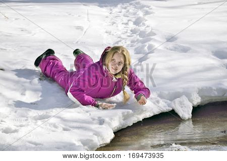 Girl with a scythe in the snow lies on the bank of the stream and drank water from it