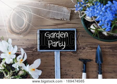 Sign With English Text Garden Party. Sunny Spring Flowers Like Grape Hyacinth And Crocus. Gardening Tools Like Rake And Shovel. Hemp Fabric Ribbon. Aged Wooden Background