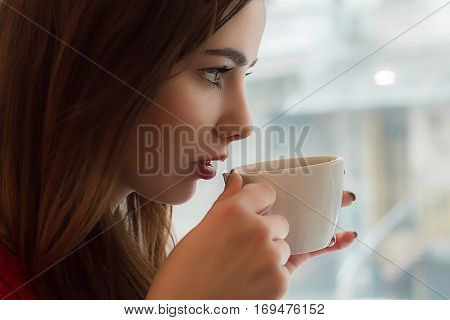 Young girl drinks tea from smal cup in cafe with big window