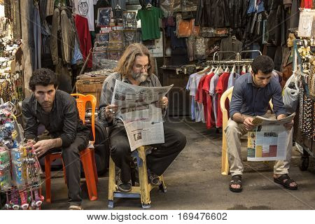 TEHRAN IRAN - AUGUST 14 2016: Iranian merchants reading newspapers in Farsi in Tehran main bazaar