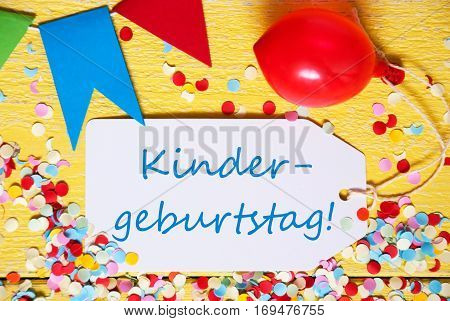 White Label With German Text Kindergeburtstag Means Children Birthday Party. Close Up Of Party Decoration Like Streamer, Confetti And Balloon. Flat Lay Or Top View. Yellow Wooden Background