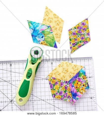 Pieces of quilt with rotary knife and ruler on white surface top view