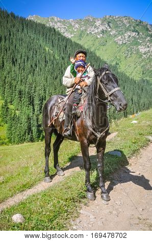 Child With Father On Horse In Kyrgyzstan