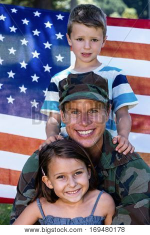American soldier reunited with his son and daughter in front of american flag