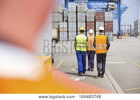 Full-length rear view of workers walking in shipping yard