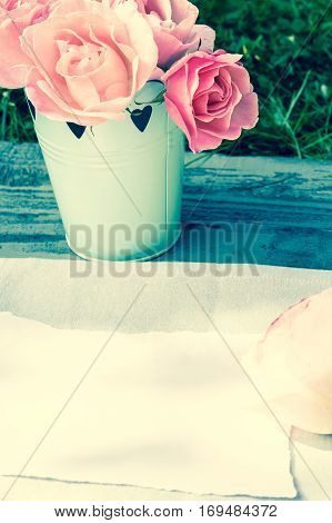 Romantic pink roses in a vase and white paper with copy space
