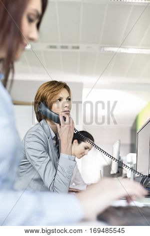 Young businesswoman using landline phone in office
