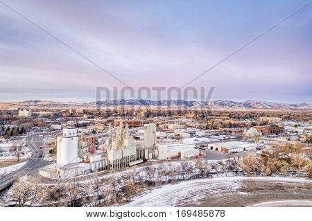 Downtown of Fort Collins, Colorado, at cold winter dawn - aerial cityscape with Poudre River in front and Rocky Mountains in background..