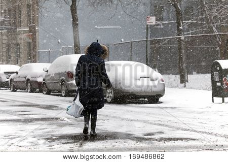 BRONX NEW YORK - JANUARY 7: Woman crossing street during snow storm. Taken January 7 2017 in New York.