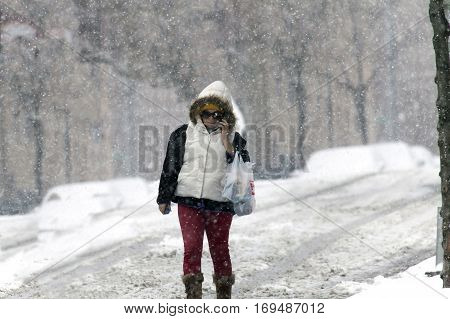 BRONX NEW YORK - JANUARY 7: Woman using cel phone during snow storm. Taken January 7 2017 in New York.