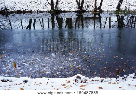 Ice on river, orange leaves on ice and reflection of trees in water. Winter landscape.