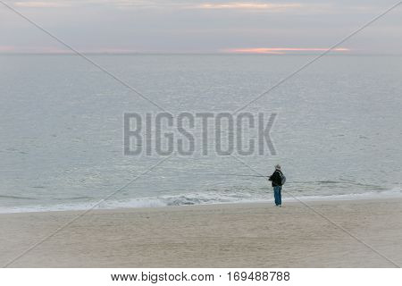 Man fishing at the beach of the Sea of Cortez in Mexico at sunrise.