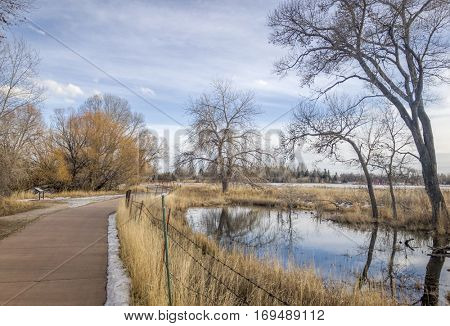 recreational and commuting bike trail along the Poudre River in Fort Collins, Colorado, typical winter scenery with some snow