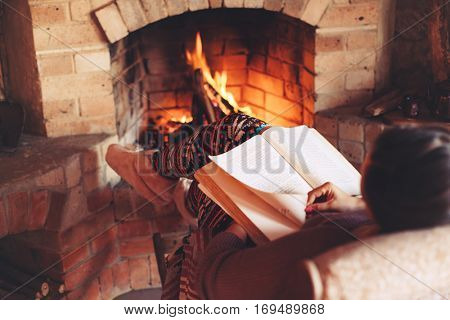 Woman reading book and relaxing by the fire place some cold evening, winter weekends, cozy scene