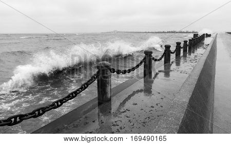 Waves crashing over pier pillars and chain at shoreline rain and windy tempest in black and white