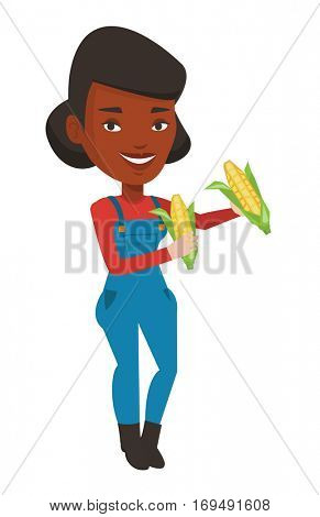 Smiling african-american farmer collecting corn. Happy female farmer holding a corn cob. Cheerful farmer standing a corn cob in hands. Vector flat design illustration isolated on white background.