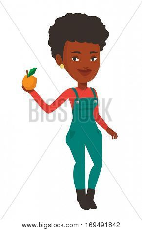 Happy african-american farmer holding an orange. Smiling farmer collecting oranges. Farmer standing with an orange in hand. Vector flat design illustration isolated on white background.