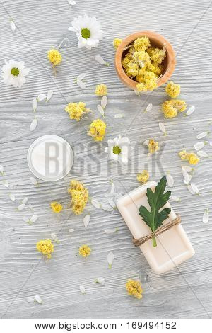 organic cosmetics with camomile on wooden background top view.