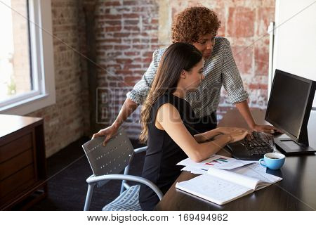 Two Businesswomen Working On Computer In Office