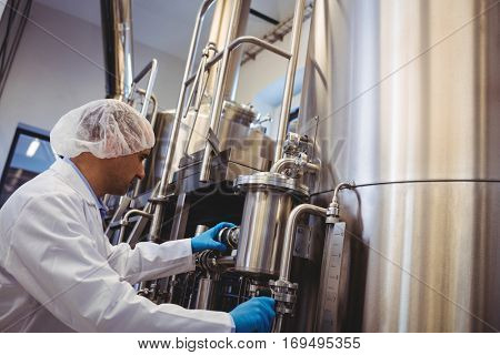 Low angle view of manufacturer working at storage tanks in brewery