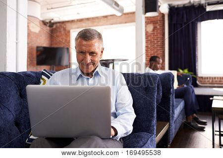 Businessmen Working On Sofas In Relaxation Area Of Office
