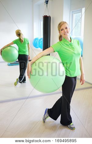 Happy young woman poses with fitball in fitness center in sunny room