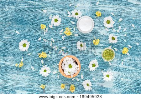 organic cosmetics with camomile on blue background top view.