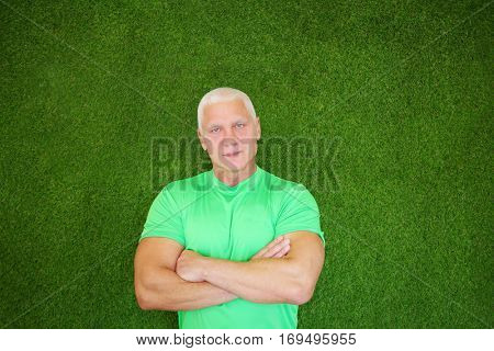 Middle-age man in t-shirt stands near green wall with crossed arms