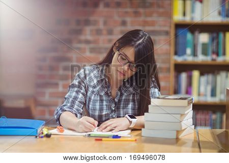 Female student writing notes at desk in library