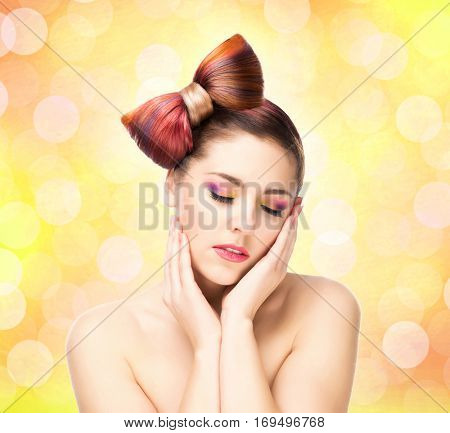 Beautiful sensitive girl with a bow haircut and colorful make-up on bubble background.