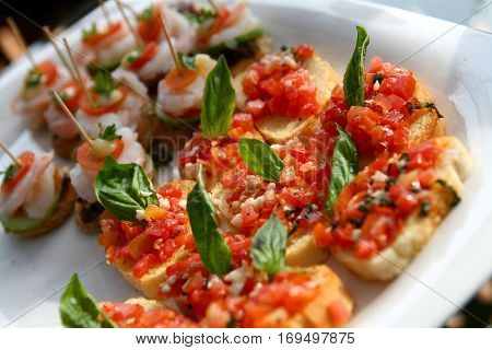 Canape cocktail tomatoes shrimp on fresh bread pesto as topping (selective focus at front)