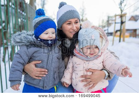 Winter portrait of happy mother with toddler twins