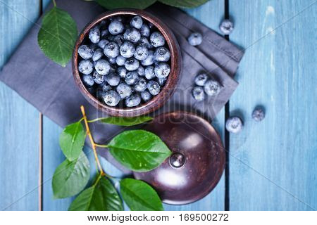 Freshly picked blueberries in metal bowl. Juicy and fresh blueberries with green leaves on blue wooden table. Blueberry on wooden background. Concept for healthy eating and nutrition.