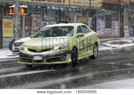BRONX NEW YORK -JANUARY 7: Apple Green Boro Taxi turns on street during snow storm. Taken January 7 2017 in New York.