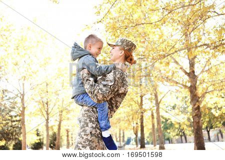 Mother soldier and little kid playing in the park