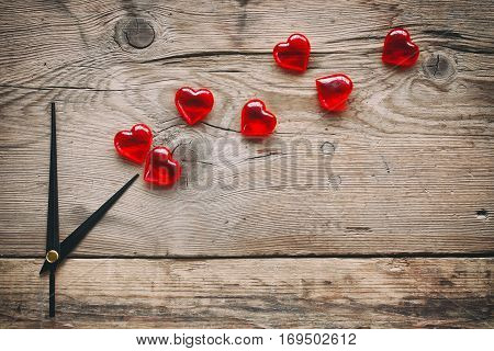 Valentine's day abstract clock and hearts on old wooden board