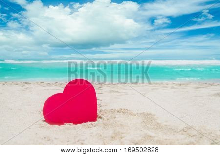 Valentine's day background with heart on the sandy Miami beach near ocean in sun day