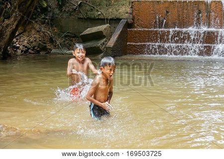 Beaufort,Sabah,Malaysia-Jan 28,2017:Kids enjoying and having fun with waterfall in Beaufort,Sabah,Borneo on 28th Jan 2017.