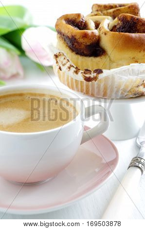 fresh tasty cinnamon roll and cup of coffee