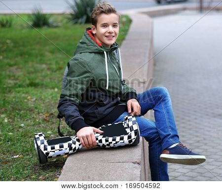 Teenager sitting on parapet with gyroscooter in autumn day