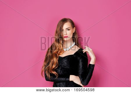 Gorgeous young woman in black evening gown on pink background